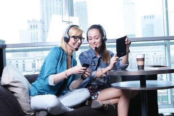 dwie dziewczyny siedzą w kawiarni i mają kurs angielskiego online