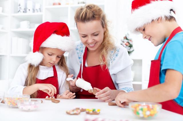 mama z dwójką dzieci uśmiechnięci dekorują pierniczki - jak przetrwać święta