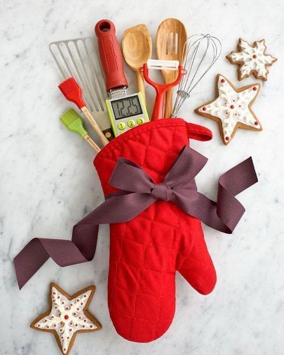 prezenty świąteczne, czerwona rękawica kuchenna z wkładką z przyborów kuchennych z bordową kokardą w towarzystwie zdobionych lukrem pierniczków w kształcie gwiazdek i płatków śniegu