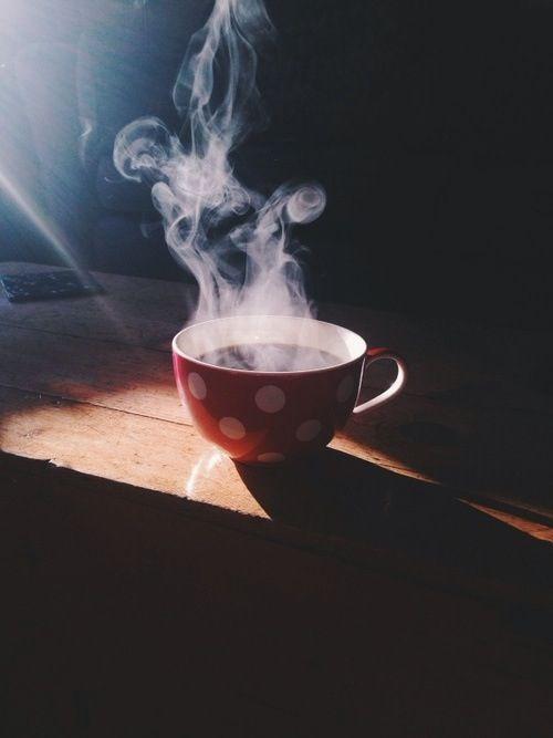 czerwona filiżanka w białe grochy z gorącą herbatą w promieniach słońca