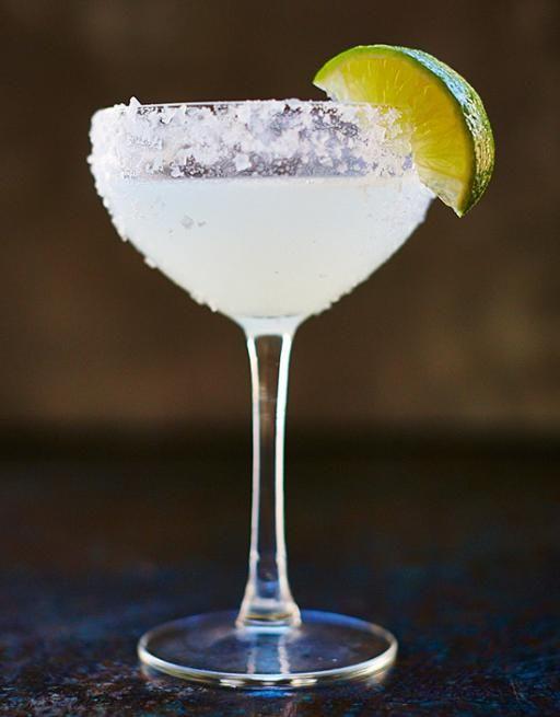 drink margerita podany w wysokim pękatym kieliszku z brzegami obsypanymi cukrem i udekorowany ćwiartką limonki